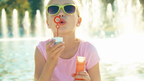 Close-Up-Portrait-Laughing-Girl-Blowing-Soap-Bubbles-On-Fountain-Background