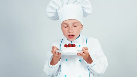 Close-Up-Portrait-Little-Chef-Baker-Holds-Meringue-Cake-Sniffing-It-And-Gives