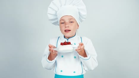 Close-Up-Portrait-Little-Chef-Baker-Holds-Meringue-Cake-Sniffing-It-And-Smiling