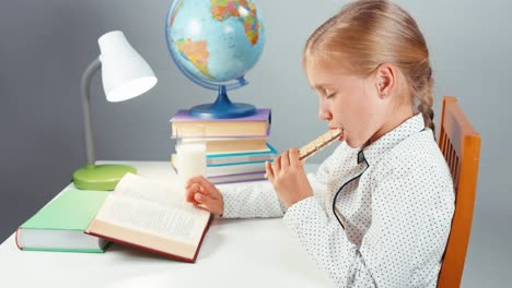Close-Up-Portrait-School-Girl-7-8-Years-Reading-Book-And-Eating-Wafer
