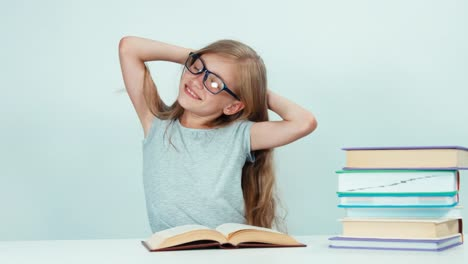 Close-Up-Portrait-Schoolgirl-Stretching-At-Camera-And-Reading-Book-At-The-Table
