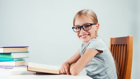 Close-Up-Portrait-Student-Girl-7-8-Years-Reading-Book-And-Smiling-At-Camera