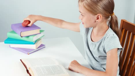 Close-Up-Portrait-Student-Girl-Child-7-8-Years-Reading-Book-And-Eating-Fruit