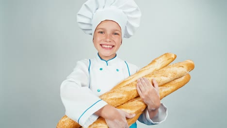 Close-Up-Portrait-Young-Baker-Girl-Child-Holds-Bread-Baguettes-And-Smiling
