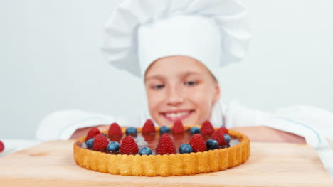 Close-Up-Portrait-Young-Baker-Looking-At-Chocolate-Cake-With-Fruits-Raspberries