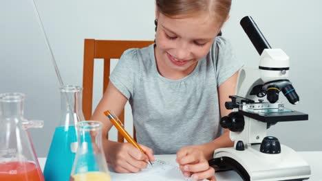 Cerrar-Retrato-Joven-Químico-Chica-Utilizando-Microscopio-Y-Algo-Escrito