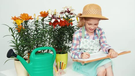 Closeup-Portrait-Child-Girl-Sitting-Near-Flowers-And-Drawing-On-Drawing-Board