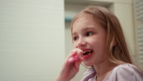 Closeup-Portrait-Girl-7-Years-Old-Brushing-Her-Teeth-In-A-Bathroom