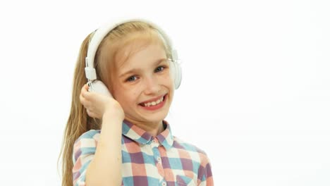 Closeup-Portrait-Girl-7-8-Years-Old-Listening-Music-And-Dancing-On-The-White