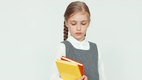 Cute-Schoolgirl-7-8-Years-Holding-Books-On-White-Background-And-Smiling-With