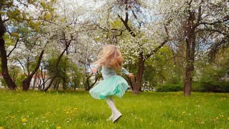 Linda-Niña-De-7-8-Años-En-Falda-Azul-Girando-En-El-Parque-En-El-Sprinng