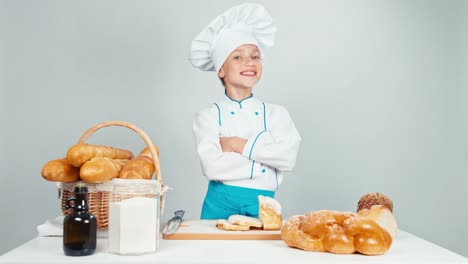 Cute-Baker-Girl-Standing-Near-Kitchen-Table-With-Bakery-Products-Isolated-On