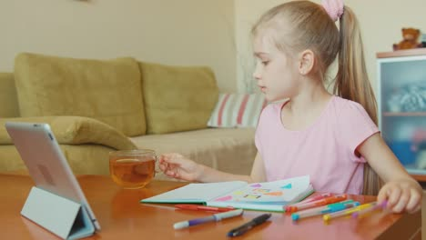 Cute-Girl-7-Years-Old-Drawing-In-A-Notebook-And-Drinking-Tea