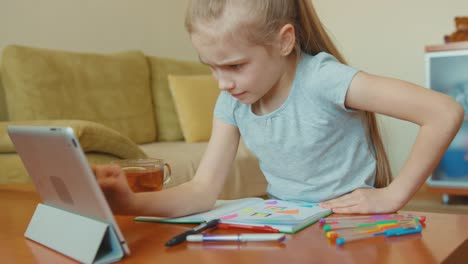 Cute-Girl-7-Years-Old-Drawing-In-A-Notebook-And-Looking-At-Tablet-PC