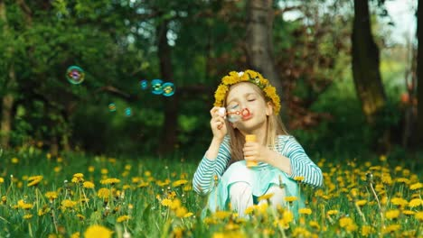 Cute-Girl-7-8-Years-Blowing-Soap-Bubbles-And-Sitting-On-The-Glade-Of-Dandelions