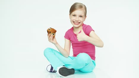Cute-Girl-7-8-Years-Holding-Muffin-On-White-Background-Thumb-Up-Ok