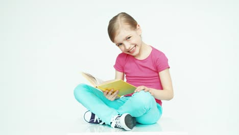 Cute-Girl-7-8-Years-Old-Reading-Book-On-White-Background-Thumb-Up-Ok