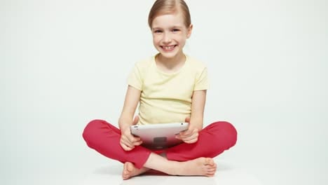 Cute-Girl-7-8-Years-Old-Using-Tablet-PC-On-White-Background-And-Smiling
