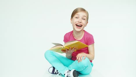 Cute-Girl-7-8-Years-Reading-Book-And-Laughing-On-White-Background