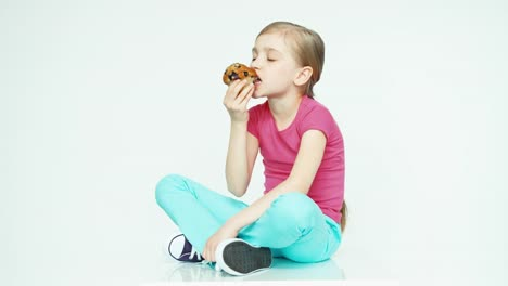 Cute-Girl-Child-7-8-Years-Eating-Muffin-And-Looking-At-Camera-And-Sitting
