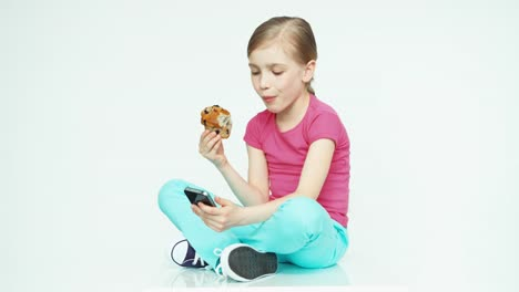 Cute-Girl-Child-7-8-Years-Eating-Muffin-And-Using-Mobile-Phone