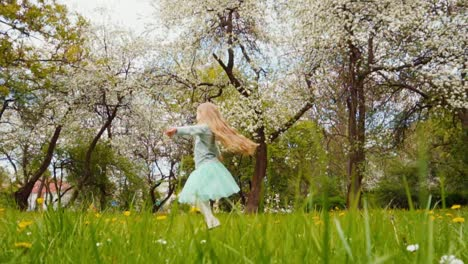 Cute-Girl-Child-Spinning-In-The-Park-In-The-Spring-Near-A-Blooming-Trees