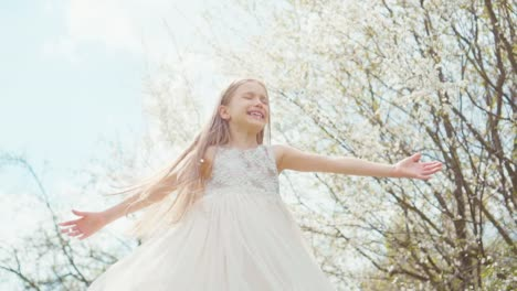 Cute-Girl-Spinning-In-A-Dress-On-A-Background-Of-Blooming-Trees-Slow-Motion