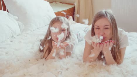 Cute-Happy-Girls-Playing-With-Fluff-And-Feathers-In-The-Bed-Slowmotion