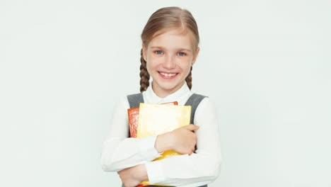 Cute-Happy-Schoolgirl-7-8-Years-Hugging-Books-On-White-Background-Smiling