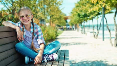 Cute-Schoolgirl-7-8-Years-In-Sunglasses-Sitting-On-The-Bench-And-Waving-Hand