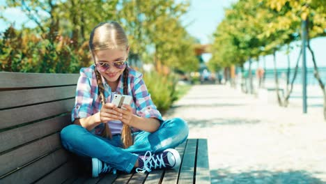 Cute-Schoolgirl-7-8-Years-In-Sunglasses-Using-Cell-Phone-Sitting-On-The-Bench