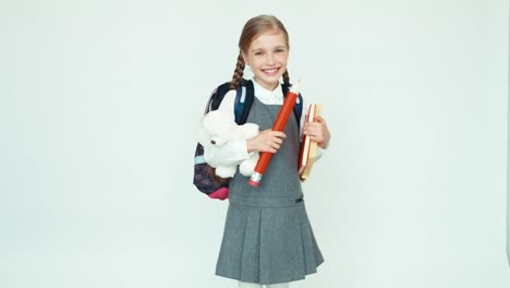Cute-Schoolgirl-7-8-Years-With-Backpack-Holding-Books-And-Big-Pencil-And-Teddy