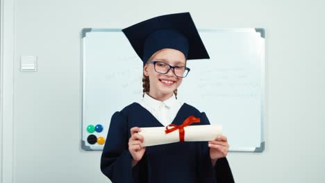 Cute-Student-7-8-Years-Graduate-In-The-Mantle-And-Hat-Holding-Diploma