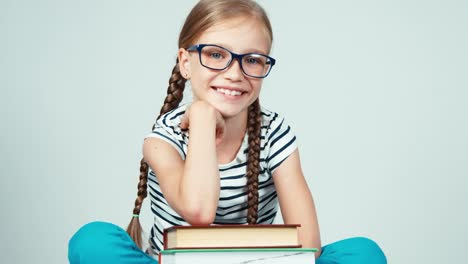 Extreme-Close-Up-Portrait-Girl-7-8-Years-Old-Sitting-Near-Stack-Of-Book