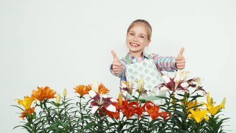 Flowergirl-Child-Smiling-With-Teeth-At-Camera-On-White-Background-Thumb-Up-Ok
