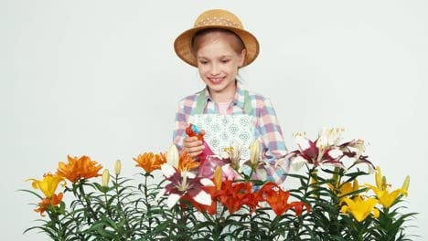 Flowergirl-In-Hat-Sprinkling-Flowers-At-Camera-And-Smiling-With-Teeth-On-White