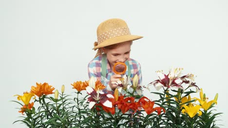 Flowergirl-Using-Magnifier-Looking-At-Flowers-And-Smiling-With-Teeth-On-White