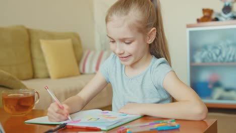 Girl-7-Years-Old-Drawing-In-A-Notebook-And-Smiling-At-Camera