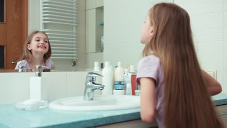 Girl-7-Years-Old-Preening-Before-The-Mirror-In-The-Bathroom