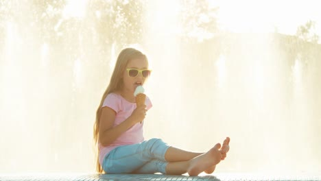 Girl-7-8-Years-Eating-Icecream-On-Fountain-Background-At-Sunny-And-Hot-Day