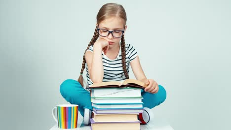 Girl-7-8-Years-In-Glasses-Reading-Book-And-Smiling-At-Camera-With-Teeth-On-White