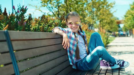 Girl-7-8-Years-In-Sunglasses-Sitting-On-The-Bench-And-Smiling-At-Camera-In-Park