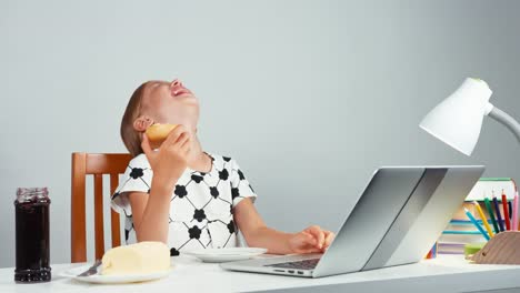 Girl-7-8-Years-Laughing-Eating-Bread-With-Jam-Butter-And-Using-Laptop-Sitting