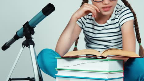 Girl-7-8-Years-Old-Reading-Book-Near-Telescope-And-Smiling-With-Teeth