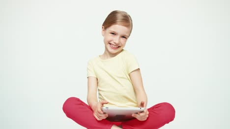 Girl-7-8-Years-Old-Using-Tablet-PC-And-Laughing-And-Sitting-On-The-White