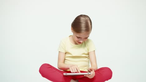 Girl-7-8-Years-Old-Using-Tablet-PC-And-Sitting-On-The-Floor-On-White-Background