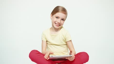 Girl-7-8-Years-Old-Using-Tablet-PC-Sitting-On-The-White-Background