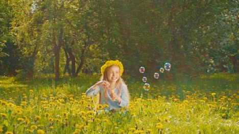 Girl-7-8-Years-Sitting-In-The-Grass-And-Blowing-Soap-Bubbles-In-The-Park