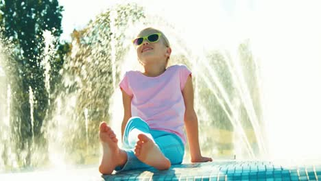 Girl-7-8-Years-Sitting-Near-Fountain-At-Sunny-Day-Child-In-Sunglasses-Smiling