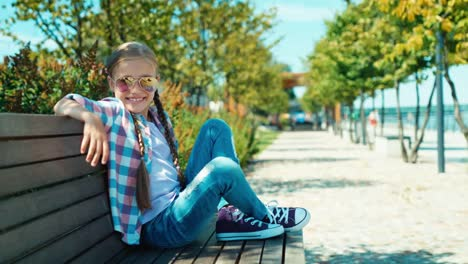 Girl-7-8-Years-Sitting-On-The-Bench-And-Smiling-At-Camera